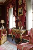 Artistic interior in old English salon with walls and pelmets in shades of pink and Rococo console table