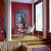 Traditional living room with table and chairs on platform and walls painted dusky pink with white stucco columns