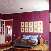 Bedroom with double bed against wall painted deep violet in traditional setting