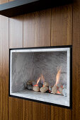 Gas fire with marble cladding and pebbles integrated into wooden wardrobe doors