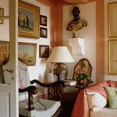 Richly decorated corner of French-style living room with bust and impressionist paintings