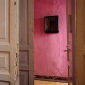 Blick durch offene Tür auf pinkfarbene Wand mit Bild im Flur einer Altbauwohnung