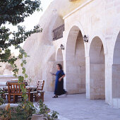 Woman walking to terrace seating area of Oriental house with arcades