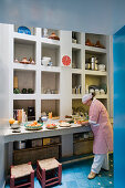 View through doorway of woman preparing food on kitchen counter in front of masonry shelving