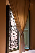 Gathered curtain in front of window with Moroccan-style grille