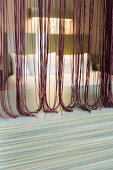 View through thread curtain in various shades of red
