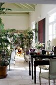 Mediterranean interior with elegant desk and potted plants in front of transparent wooden screen