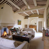 Open living room in Mediterranean country home with upholstered couch and coffee table in front of a fireplace