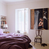 Simple bedroom with antique chair in front of a modern picture on the wall