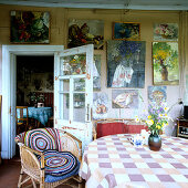 Collection of oil paintings on plain wooden wall; round crocheted blankets on wicker chair and fresh meadow flowers on table in foreground