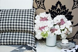 White hydrangeas in small vase next to scatter cushions and against brocade wallpaper