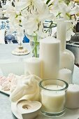 Still-life of white candles and orchids on marble table