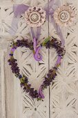 Decorative, heart-shaped wreath with lavender flowers on doorknob of white wardrobe with floral carved ornamentation