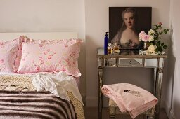 Baroque painted portrait on mirrored console table next to double bed with ruffled pillows