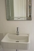 Plain ceramic sink below wall-mounted mirror with floral, etched frame