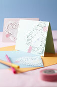 An invitation card decorated with hearts made from doilies