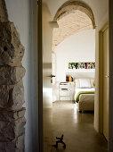 Blick vom Vorraum durch offene Tür auf Metall Stuhl neben modernem Doppelbett im Schlafraum mit Ziegel Gewölbe
