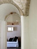 Vorraum mit Gewölbe und Blick durch Rundbogen auf Sofa mit weisser Husse und schwarzen Kissen