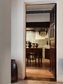 View from foyer through open door into Mediterranean kitchen with kitchen table and antique wall tiles
