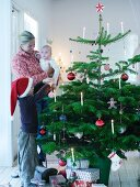 Family with child decorating Christmas tree