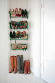 Ladies' shoes in green metal shoe racks on wall and boots on hall floor