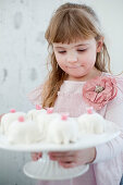 A girl in a pink dress holding a cake stand of mini cakes