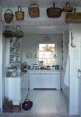 Körbe über offenen Durchgang gehängt und Blick in Landhausküche