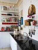 Küchenzeile mit glänzender, schwarze Arbeitsplatte in traditionellem Ambiente