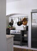 Moderner Küchenofen in Nische und an Haken hängendes Kochgeschirr