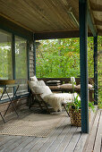 Lounger with fur blanket in pleasant seating area on veranda of summer house in garden
