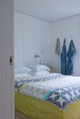View through open door of double bed with Swedish-style bed linen in white, wood-panelled bedroom