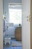 View through open door of rattan laundry basket in bathroom