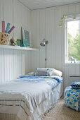 Bedspread on single bed below shelf on white, wood-clad wall in corner of room next to window