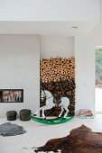 Painted rocking horse in front of firewood stacked in niche in modern interior with animal-skin rugs on white wood floor