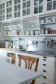 Kitchen counter with white, wall-mounted cupboards and base units in country-house style