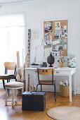 Vintage stool and trunk in front of desk against white-painted wooden wall with pinboard