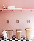 Hand-made shelf on pink wall of bathroom above ethnic washing baskets on cool chequerboard tiles