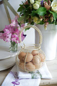 Wire basket of fresh eggs in front of bouquet of flowers