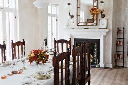 Carved wooden chairs at festively set table in simple dining room with open fireplace