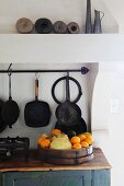 Fruit dish on plain base unit and vintage pans hanging on wall