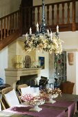 Decorated metal chandelier above dining table with flower arrangements in bowls in open-plan foyer with staircase and gallery