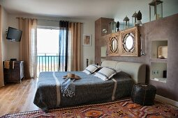 Double bed against masonry partition with wall-mounted mirrors and open balcony door with sea view