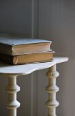 Two hardback books on old wooden shelves with decorative uprights