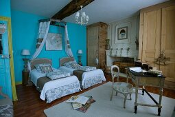 Detailed interior design in country-house bedroom - twin beds with pale, patchwork-style fabrics against wall painted light blue