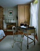 Pale colours and natural wood in bedroom with newly upholstered antique chair at antique bureau