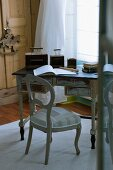 Vintage writing desk with original paintwork and wooden chair with patchwork-style upholstered seat