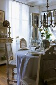 Ornate wooden chairs with woven seats and backs around festively set table below antique chandelier