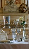 Table set in pale colours with etched glasses, pebbles and white rose; natural wood antique dresser in background
