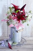 Bouquet of lilies and wild carrot in old milk can