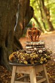 Small crown and autumn wreath on stool in woodland